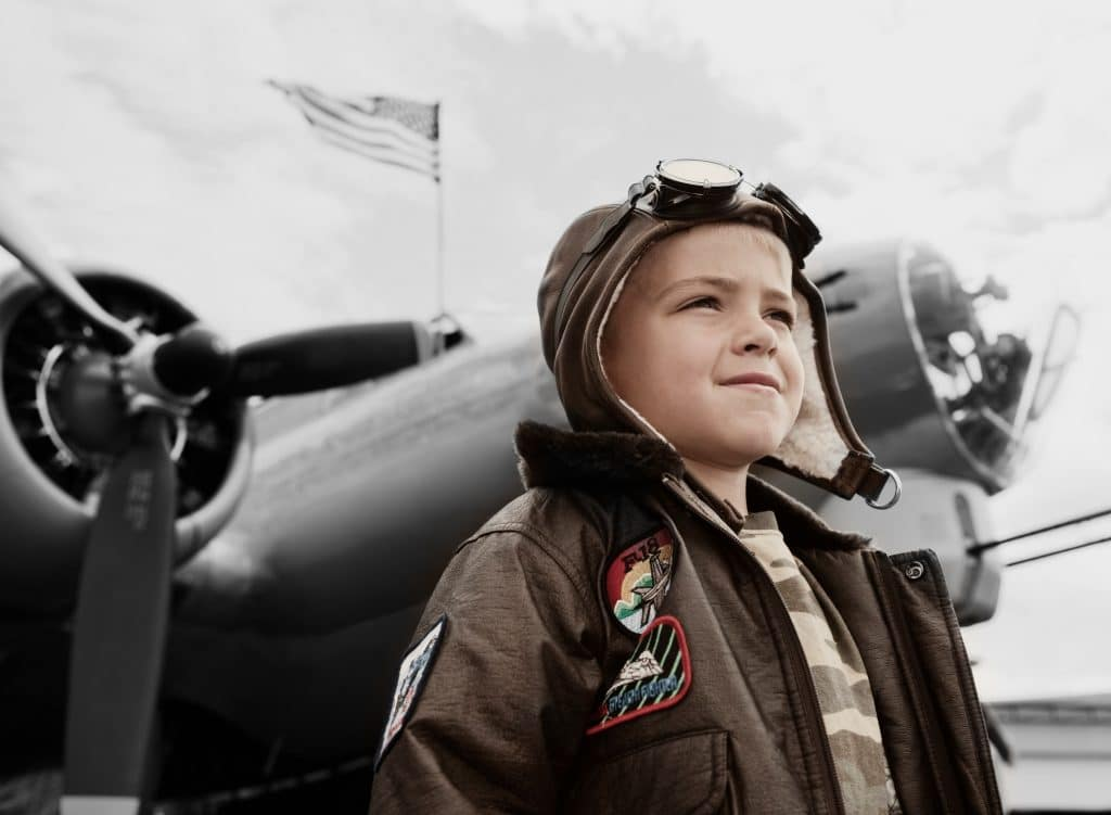 young boy in flying hat and goggles standing in front of aeroplane