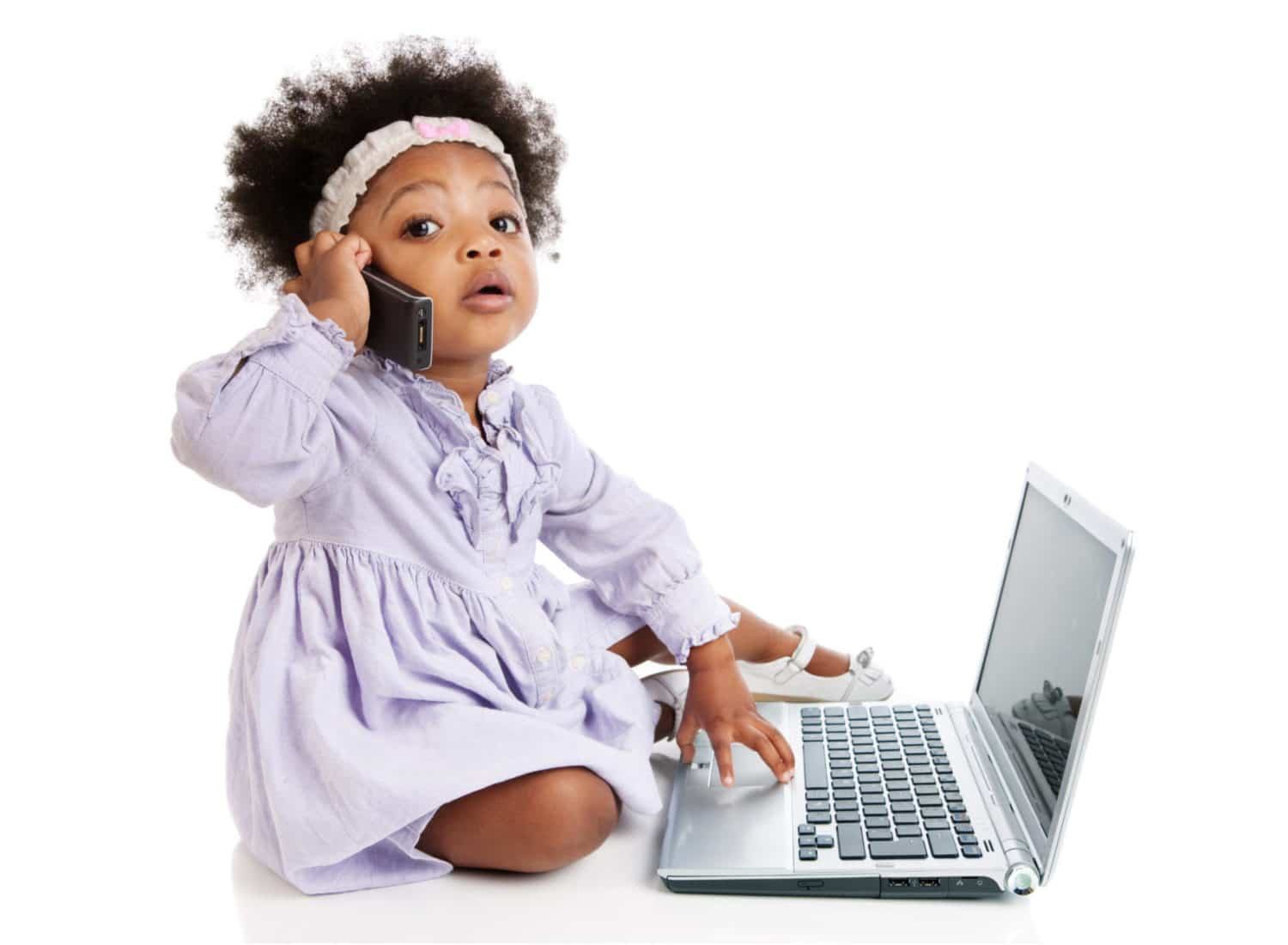 small child in purple dress sitting on floor with a telephone to her ear, touching a laptop - communication app