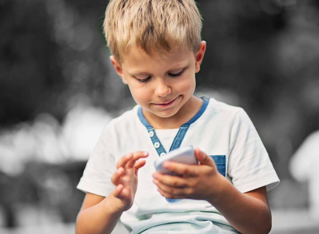 child in white t shirt, holding and looking at a mobile phone, interactive display