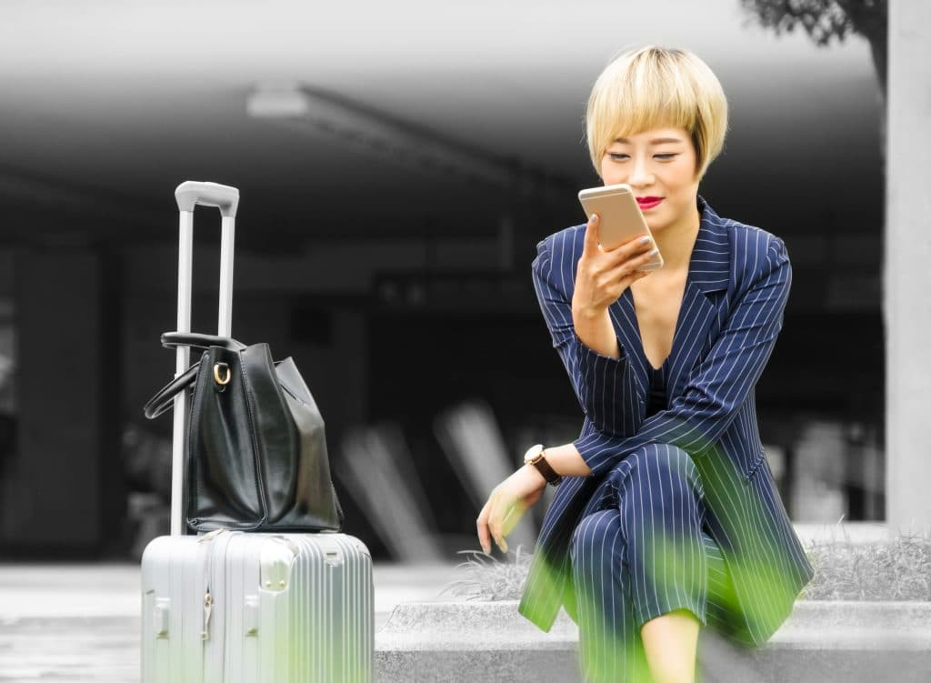 lady sitting on the path kwith suitcase next to her, looking and smiling at mobile phone - leave planner