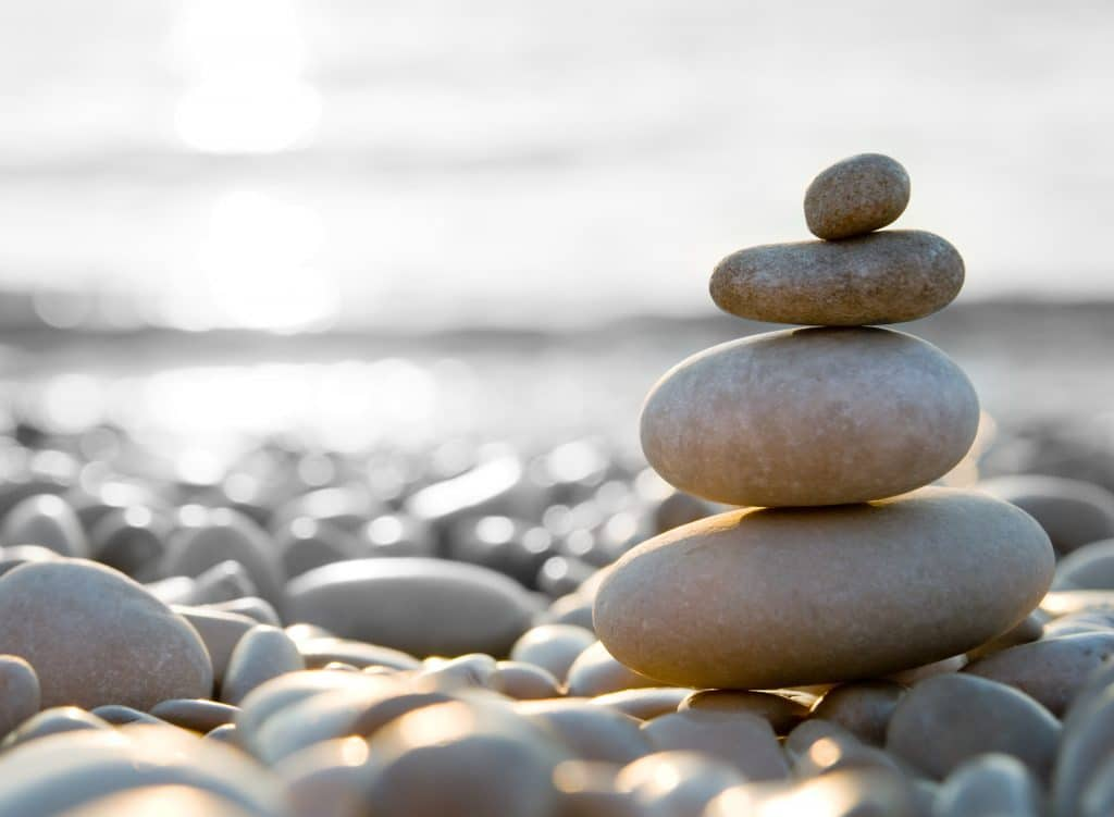 stacked pebbles on a pebble base floor, water in background